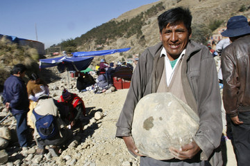 A native Bolivian man carries a rock he chose as part of the celebration of the Virgin of Urkupina on the outskirts of La Paz
