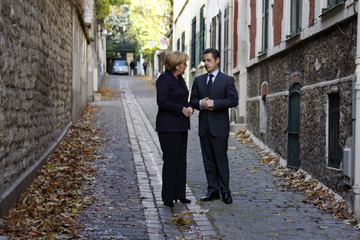 France's President Sarkozy and Germany's Chancellor Merkel speak together before a lunch during Franco-German meeting in Paris