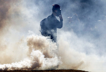 RIOTER STANDS IN A CLOUD OF TEAR GAS.