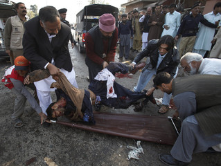 Men lift the body of a security official who was killed at the site of a suicide bomb blast at a court house in Peshawar