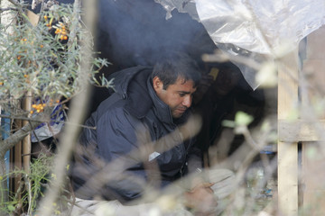 An asylum seeker warms himself at a shelter built in the middle of the woods to offer protection against low temperatures, near the harbour of Calais