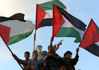 PALESTINIANS HOLD FLAGS IN GAZA DEMONSTRATION.