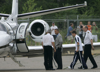 England's soccer star Owen guarded by pilots and security men walks to plane at airport in Baden-Baden