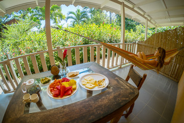 Table with breakfast and fruits and woman relaxing in the hammock in a terrace with tropical garden view
