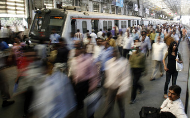 Commuters make their way on the platform at the Churchgate train station in Mumbai