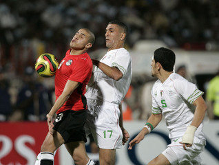 Egypt's Mohamed Zidan fights for the ball with Algeria's Samir Zaoui and Rafik Halliche during their World Cup 2010 qualifying soccer match in Khartoum