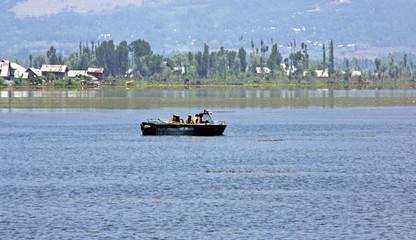 Indian policemen patrol the Dal Lake in a motorboat in Srinagar