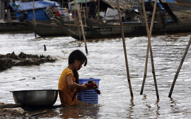 A Cambodian girl washes her clothes in the Mekong river in Kandal province