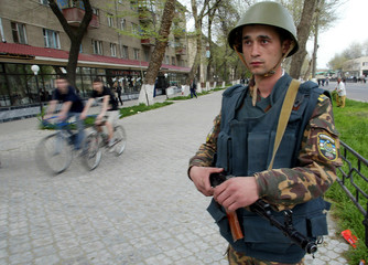 CYCLISTS PASS UZBEK SOLDIER GUARDING A CROSSROAD IN TASHKENT.