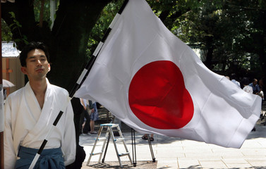 Shinto priest stands near Japanese flag at Yasukuni Shrine, a shrine for war dead seen by many in Asia as symbol of Japan's past militarism, in Tokyo