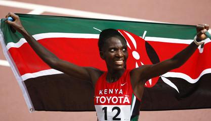 Kenya's Catherine Ndereba poses with the Kenyan national flag after winning the women's marathon at the 11th IAAF World Athletics Championship in Osaka