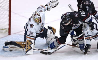 Oilers goalie Roloson gets his leg out to block puck as Canucks Kesler moves in for rebound during first period NHL play in Vancouver