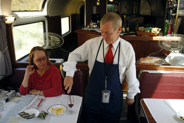 Amtrak train attendant Richard Newberry serves wine to a passenger aboard the Coast Starlight Amtrak train during a wine tasting in California