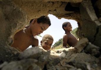 Venezuelan child laborers are seen through hole in wall.