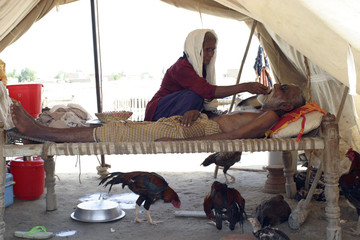 Woman feeds sick husband in flooded area of Mehar district