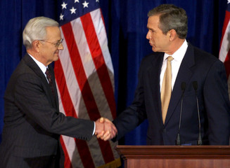 President-elect George W. Bush (R) shakes hands with businessman Paul O'Neill after nominating him a..