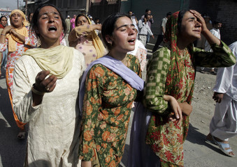 Kashmiri women cry during funeral of Wani, Kashmiri truck driver, in Panthachowk on outskirts of Srinagar