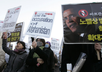 Anti-war activists chant slogans at a rally in Seoul