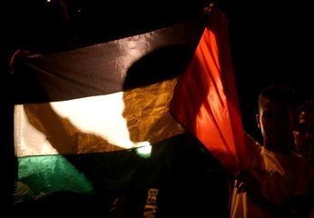 Palestinians hold a Palestinian flag during a memorial ceremony for Yasser Arafat death, in east Jer..