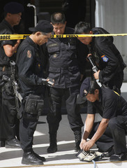 Members of an elite Philippine police team look at a wallet after a hostage rescue in Taguig City, south of the Philippine capital Manila