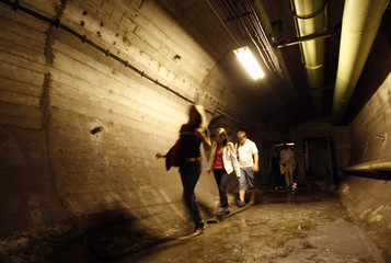 Visitors walk in an underground nuclear shelter built in the early 1950s in the centre of Budapest