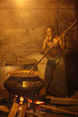 A man cooks sweet food for the people of Anawatuna village to be eaten at the end of the night during the Dammaduwa festival