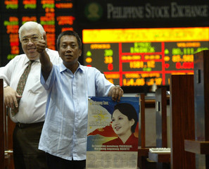 FILIPINO STOCK BROKER HOLDS A POSTER OF PRESIDENT ARROYO IN MANILA.