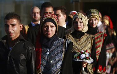 Palestinian brides and grooms participate in a group wedding ceremony in Abu Dis