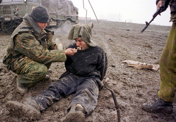 RUSSIAN SOLDIER FEEDS A CAPTURED FIGHTER IN KOMSOMOLKSKOYE.