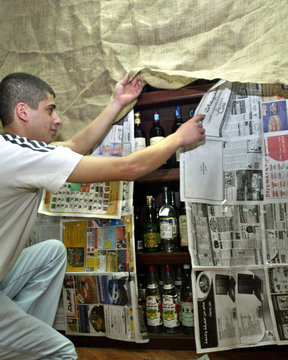 LIQUOR STORE WORKER COVERS SHELVES OF ALCOHOLIC DRINKS WITHNEWSPAPERS DURING RAMADAN.