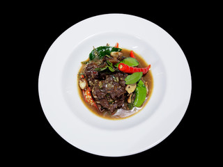 This is Fried herbal vegetables with beef in white plate on black background