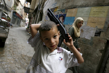 A Palestinian boy plays with his toy rifle in the refugee camp of Shatila in Beirut
