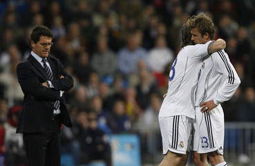 Real Madrid's Beckham is embraced by his team mate Cassano as he leaves the pitch injured during their Spanish first division soccer match against Getafe in Madrid