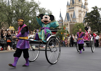Disney cartoon characters Mickey and Minnie Mouse are carried by rickshaws during a parade to celebrate upcoming Tanabata or Star festival at Tokyo Disneyland