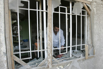 Residents are seen through an iron window grill of a damaged house after an air strike in Baghdad's Sadr City