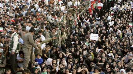 Iranian people gather to listen to Iran's President Ahmadinejad speak during rally in Shahriar