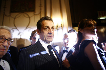 Former U.S. Secretary of State Henry Kissinger, French President Nicolas Sarkozy and his wife Carla Bruni-Sarkozy arrive at the Appeal of Conscience Foundation awards dinner in New York