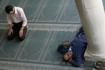 Man prays as another man sleeps at al-Husainy mosque in Amman