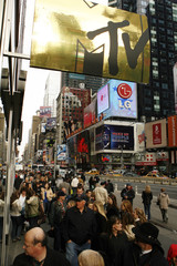 Pedestrians walk past a sign with the MTV logo on it below the MTV studios in Times Square New York