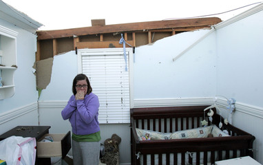 Trisha Memmer cries as she looks at what is left of her son's room after a tornado in Indiana