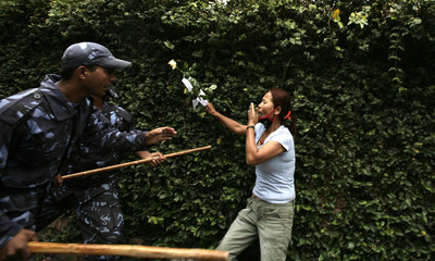 A Tibetan woman carrying a flower is stopped by the police near UN office premise in Kathmandu