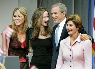 U.S. President George W. Bush stands with his wife, first lady Laura (R) and their daughters Jenna (..