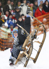 Two men in carnival dresses fall from their sledge during the traditional Bavarian sledge race called 'Schnablerrennen' in Gaissach