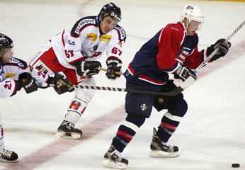 U.S.A.'S SLOAN TRIES TO CONTROL THE PUCK AGAINST SWITZERLAND'S FISCHERAND MONNET DURING THEIR ...