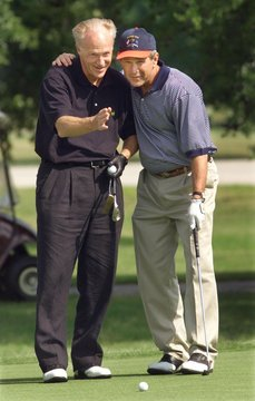 President George W. Bush (R) gets some help reading a putt on the 18th from his old college friend a..