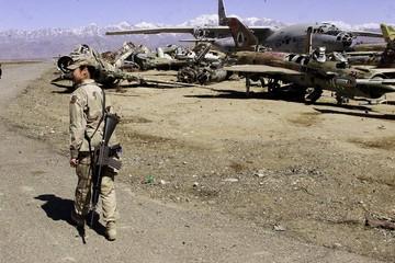 U.S.SOLDIER WALKS PAST DESTROYED RUSSIAN PLANES IN BAGRAM.