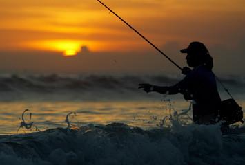 A BALINESE FISHERMAN ON LEGIAN BEACH IN BALI.