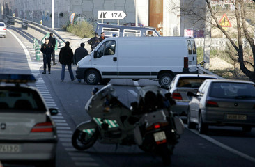 Spanish civil guards direct traffic on the A2 motorway near one of the blast sites in Madrid