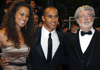 """Producer Lucas poses with Formula One driver Hamilton and guest after world premiere film """"Indiana Jones and the Kingdom of the Crystal Skull"""" in Cannes"""