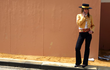 Woman wearing typical flamenco costume talks on her phone during first day of April fair in Seville